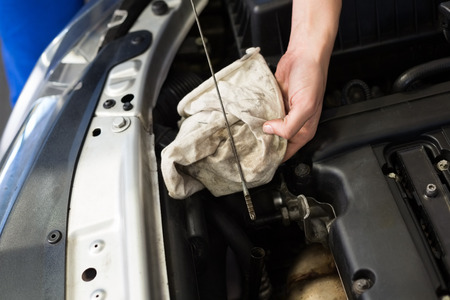 machinist: Mechanic checking the oil of car at the repair garage Stock Photo