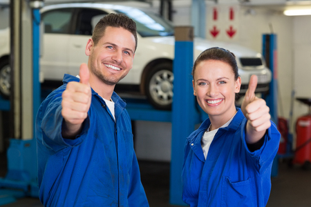 Squadra della meccanica sorridere alla telecamera a garage di riparazione