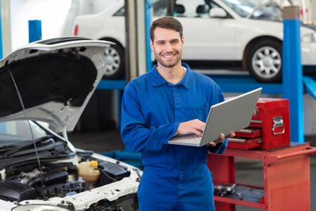 Sourire mécanicien en utilisant son ordinateur portable dans le garage de réparation Banque d'images - 36349323