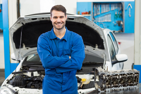 engine bonnet: Smiling mechanic looking at camera at the repair garage