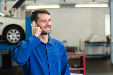 Smiling mechanic on the phone at the repair garage