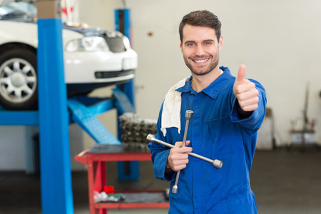 hand up: Smiling mechanic looking at camera at the repair garage