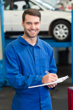 Mechanic writing on a clipboard at the repair garage Stock Photo