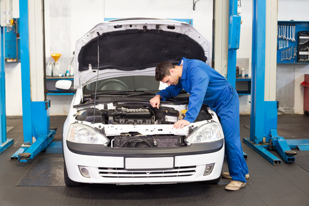 engine bonnet: Mechanic examining under hood of car at the repair garage
