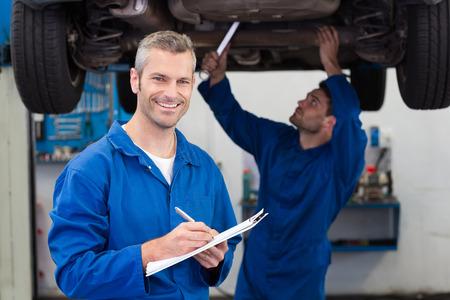 mantenimiento: Equipo de mecánicos que trabajan juntos en el garaje de reparación Foto de archivo