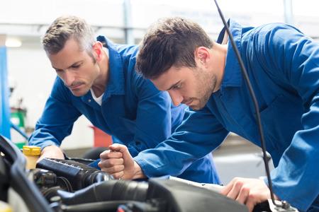 motor coche: Equipo de mecánicos que trabajan juntos en el garaje de reparación Foto de archivo