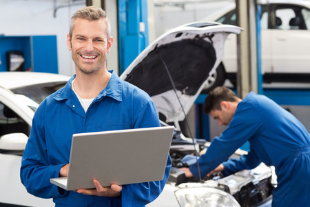 Smiling mechanic using a laptop at the repair garage photo