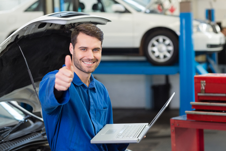 bonnet up: Mechanic using his laptop showing thumbs up at the repair garage