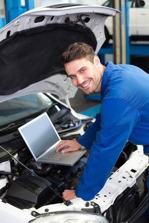 Mechanic using laptop on car at the repair garage photo