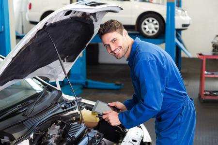Mechanik przy pomocy tabletu naprawić samochód w garażu naprawy