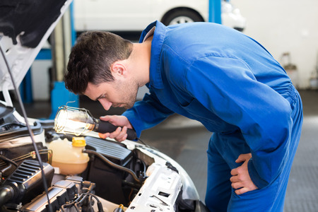 engine bonnet: Mechanic examining under hood of car with torch at the repair garage Stock Photo