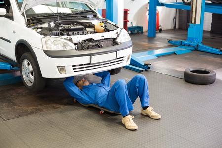garage automobile: M�canicien mensonge et travaillant sous la voiture au garage de r�paration