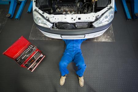 Monteur liegen en werken onder de auto bij de reparatie garage Stockfoto