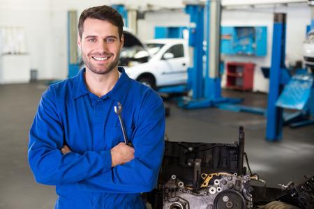 Mechanic smiling at the camera at the repair garage Stock Photo