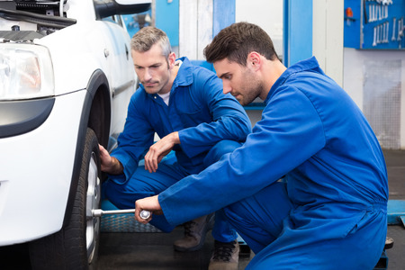 auto service: Team of mechanics working together at the repair garage