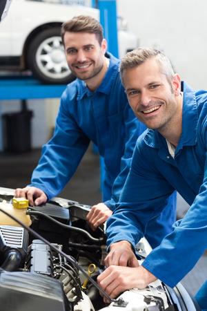 mecanico: Equipo de mecánicos que trabajan juntos en el garaje de reparación Foto de archivo