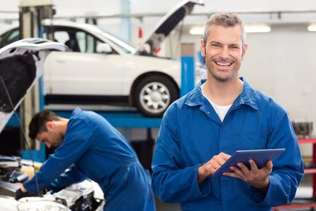 garage automobile: Sourire mécanicien en utilisant un Tablet PC dans le garage de réparation Banque d'images