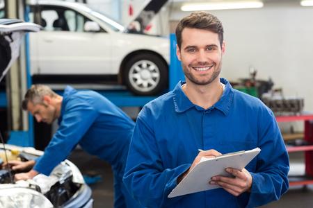 Lachende mechanische schrijven op klembord op de reparatie garage