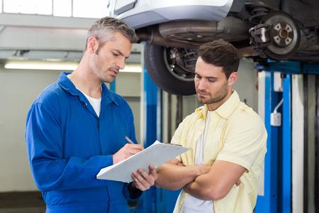service engineer: Customer listening to his mechanic at the repair garage