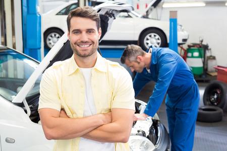mecanico: Sonriendo a la c�mara en el garaje de reparaci�n al cliente Foto de archivo