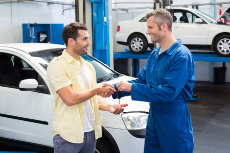 Customer shaking hands with mechanic taking keys at the repair garage photo