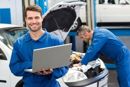 自動車修理工場でラップトップを使用してメカニックの笑みを浮かべてください。