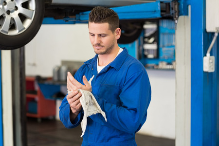 Mechanic wiping hands with rag at the repair garage Stock Photo