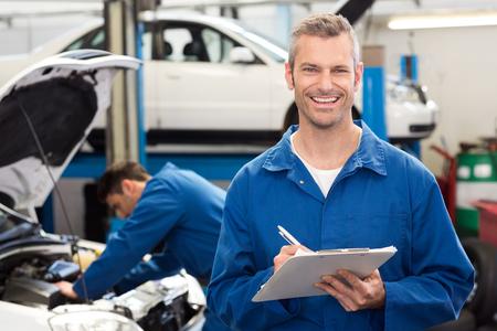 auto mechanic: Smiling mechanic writing on clipboard at the repair garage
