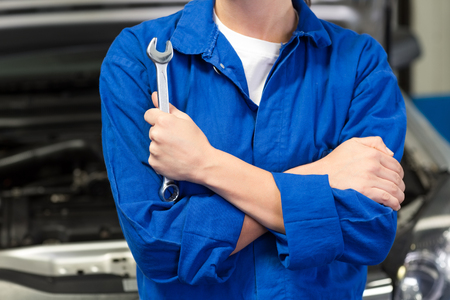 wrench: Mechanic holding wrench with crossed arms at the repair garage Stock Photo