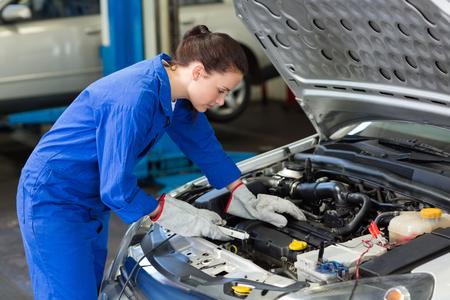 garage mechanic: Mechanic working under the hood at the repair garage Stock Photo
