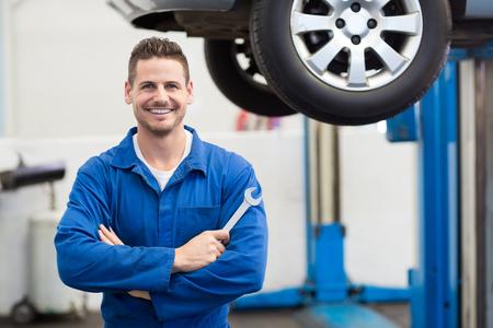 mecanico: Sonriendo a la herramienta de sujeci�n de c�mara en el garaje de reparaci�n Mec�nico
