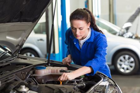 engine bonnet: Mechanic working under the hood at the repair garage Stock Photo