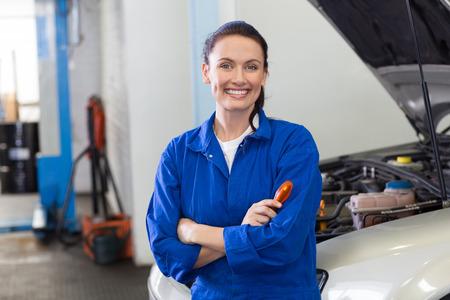 mujer trabajadora: Sonriendo a la c�mara en el garaje de reparaci�n Mec�nico Foto de archivo