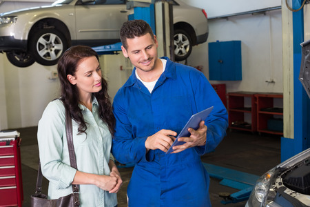 car service: Mechanic showing tablet pc to customer at the repair garage Stock Photo