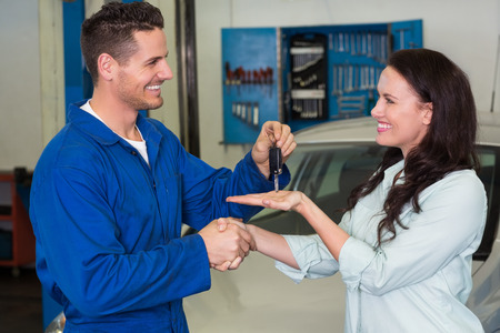 satisfied customer: Mechanic giving keys to satisfied customer at the repair garage