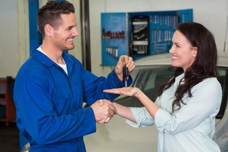 Mechanic giving keys to satisfied customer at the repair garage