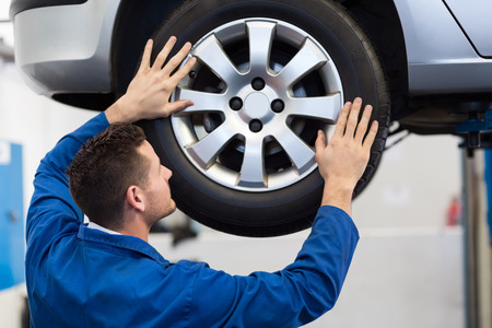 tire fitting: Mechanic adjusting the tire wheel at the repair garage Stock Photo