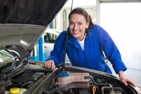 mecanico: Sonriendo a la fijación del motor de cámara en el garaje de reparación Mecánico Foto de archivo
