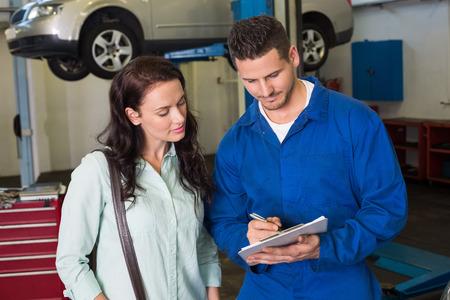 mecanico: Mec�nico y cliente hablando juntos en el garaje de reparaci�n Foto de archivo
