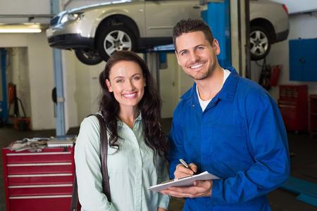 Monteur lachend naar de camera met de klant bij de reparatie garage Stockfoto