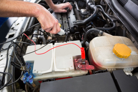 protective work wear: Mechanic working under the hood at the repair garage Stock Photo