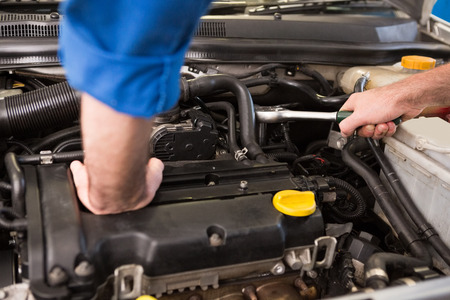 engine bonnet: Mechanic examining under hood of car at the repair garage