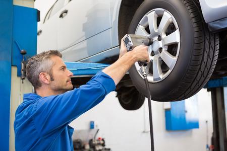 hubcap: Mechanic adjusting the tire wheel at the repair garage Stock Photo