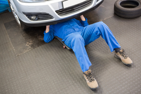 machinist: Mechanic lying and working under car at the repair garage