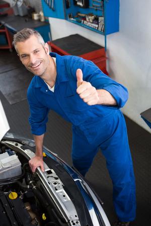 engine bonnet: Mechanic looking up at camera at the repair garage Stock Photo