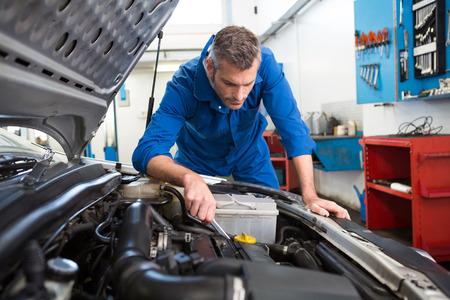 メカニック修理ガレージで車のボンネットの下を調べる