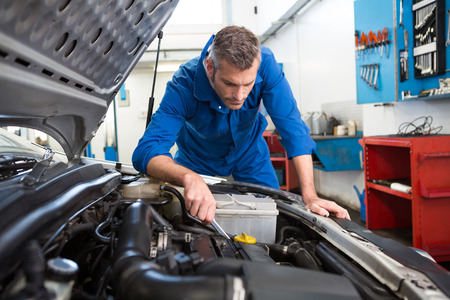 Mechanic examining under hood of car at the repair garage Imagens - 36354833