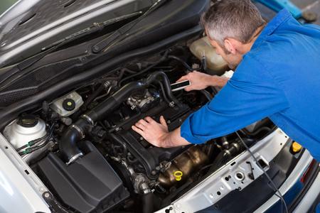 mecanico: Mec�nico que trabaja bajo el cap� en el garaje de reparaci�n Foto de archivo