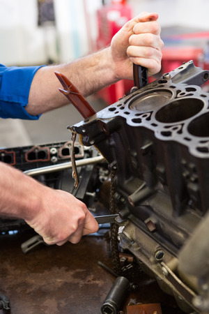 machinist: Mechanic working on an engine at the repair garage Stock Photo