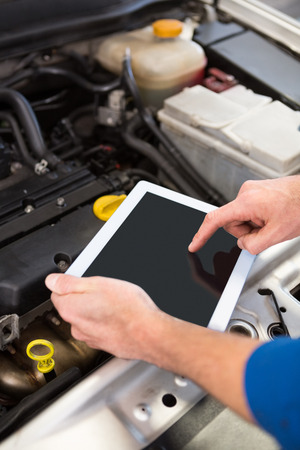 scrolling: Mechanic using tablet to fix car at the repair garage